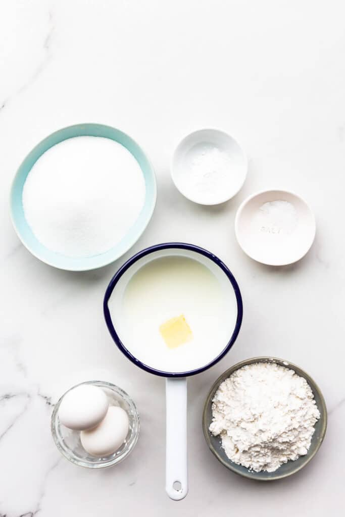 Ingredients to make an easy sponge cake called the hot milk sponge cake, measured out, including flour, eggs, sugar, baking powder, salt, and milk with butter in a saucepan.