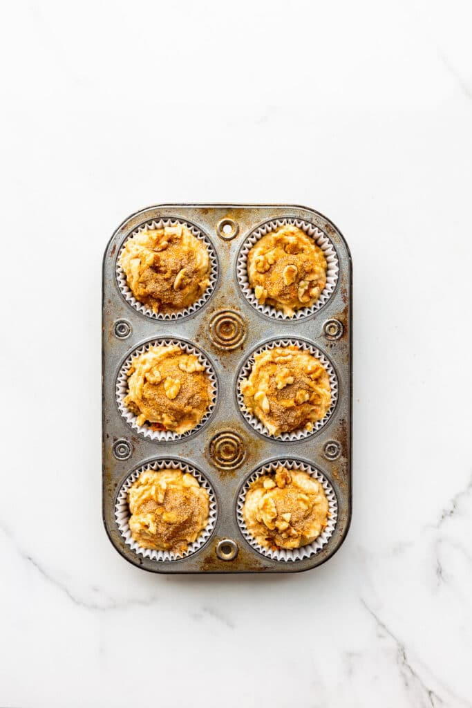 Carrot muffins topped with cinnamon sugar before baking in muffin pan with paper liners.