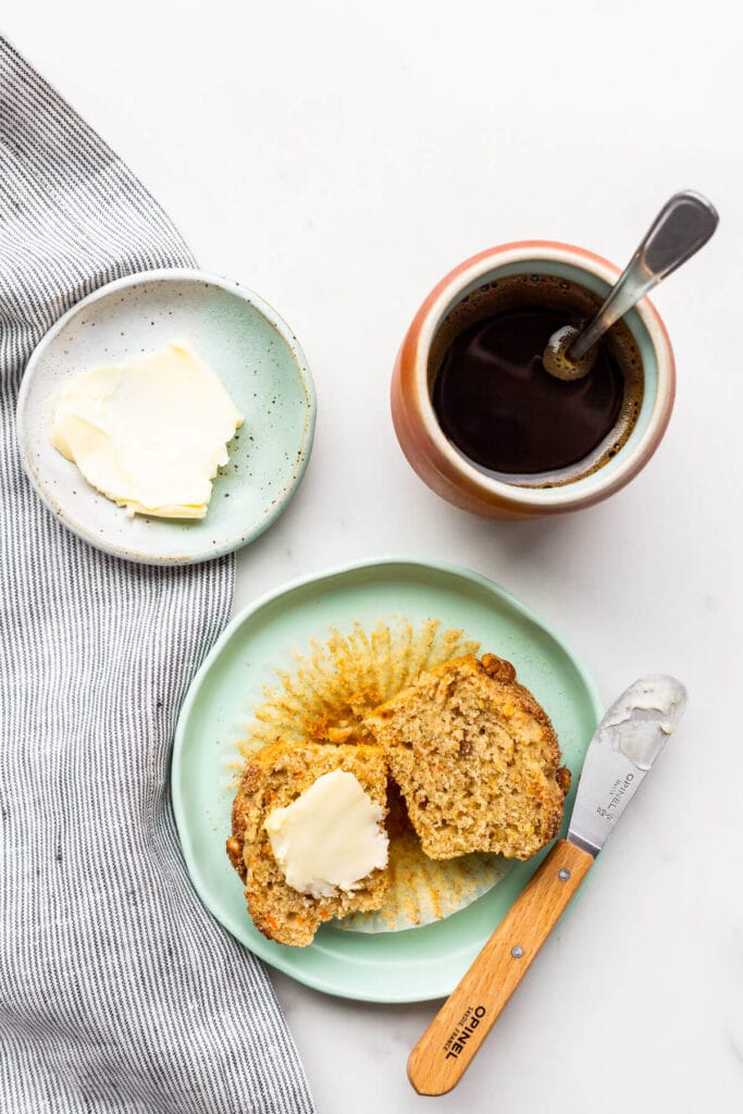Freshly baked carrot muffin on a plate, split open and buttered. Served with a cup of coffee.