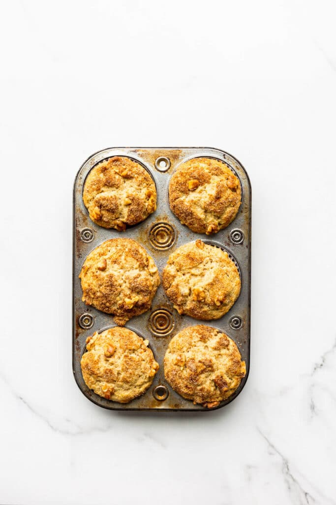 A muffin pan of carrot muffins, freshly baked and cooling.
