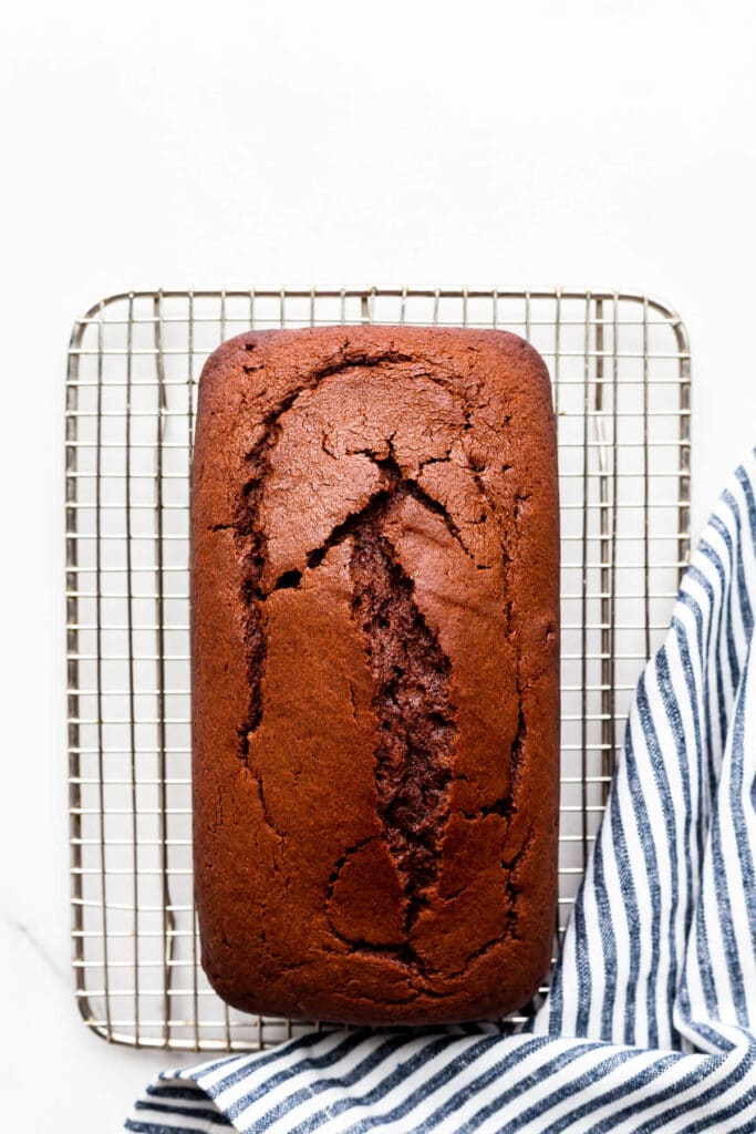 Chocolate loaf cake cooling on a wire rack with a striped linen tucked on the side.