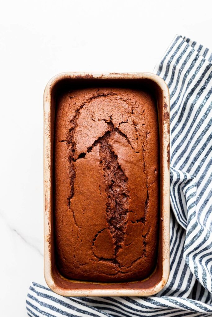 Freshly baked chocolate loaf cake still in cake pan with striped linen tucked on the side.