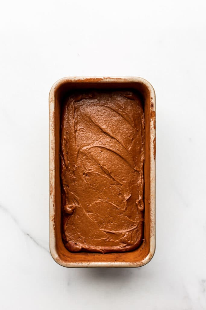 Chocolate cake batter spread evenly in a loaf cake pan, ready to be baked.