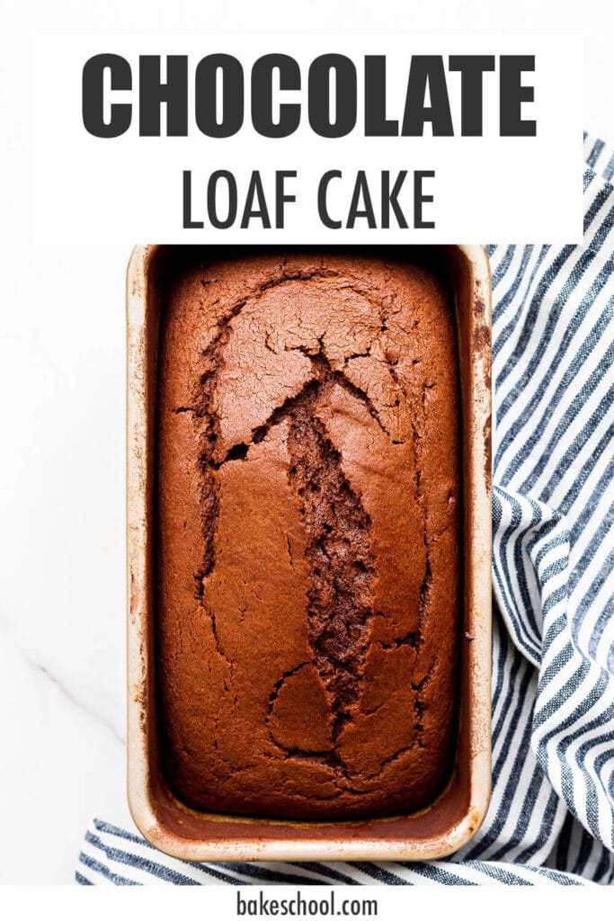 Baked chocolate loaf cake in loaf pan with striped linen tucked underneath.