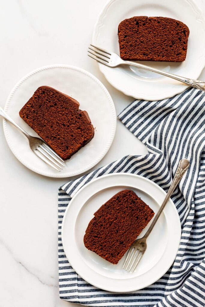 Slices of chocolate loaf cake on white plates and striped linen, ready to be served,
