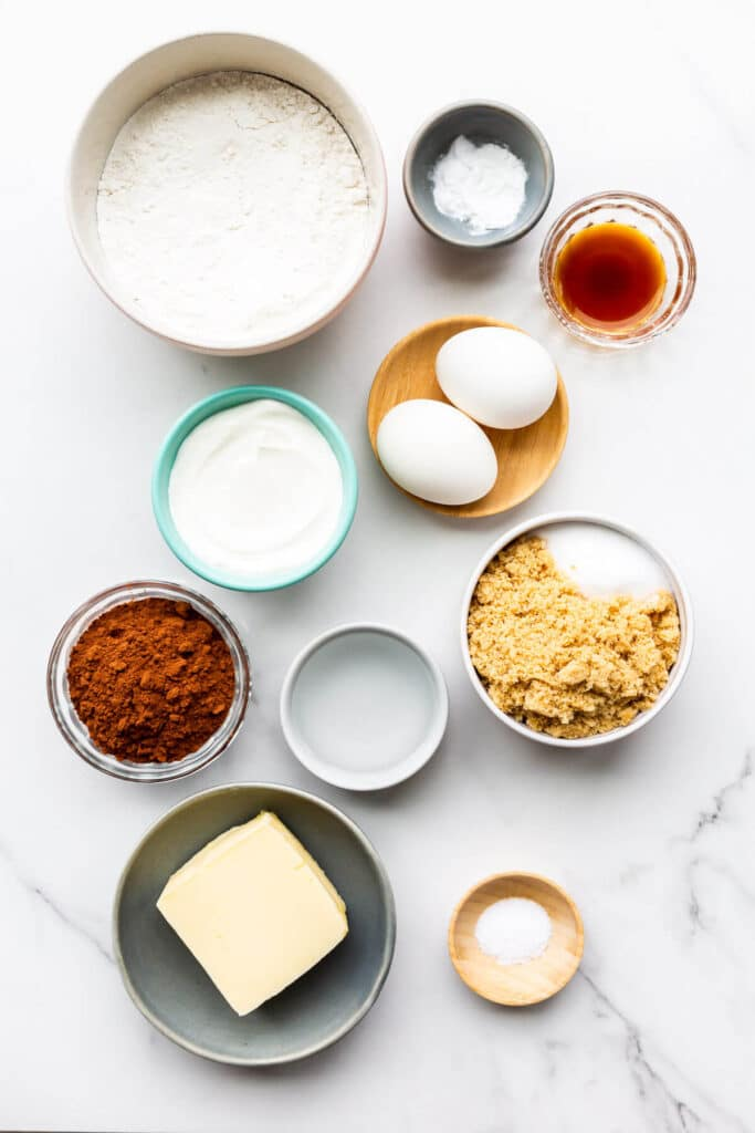Ingredients to make chocolate loaf cake measured out for baking, including butter, salt, sugar, cocoa powder, boiling water, flour, eggs, sour cream, and vanilla extract.