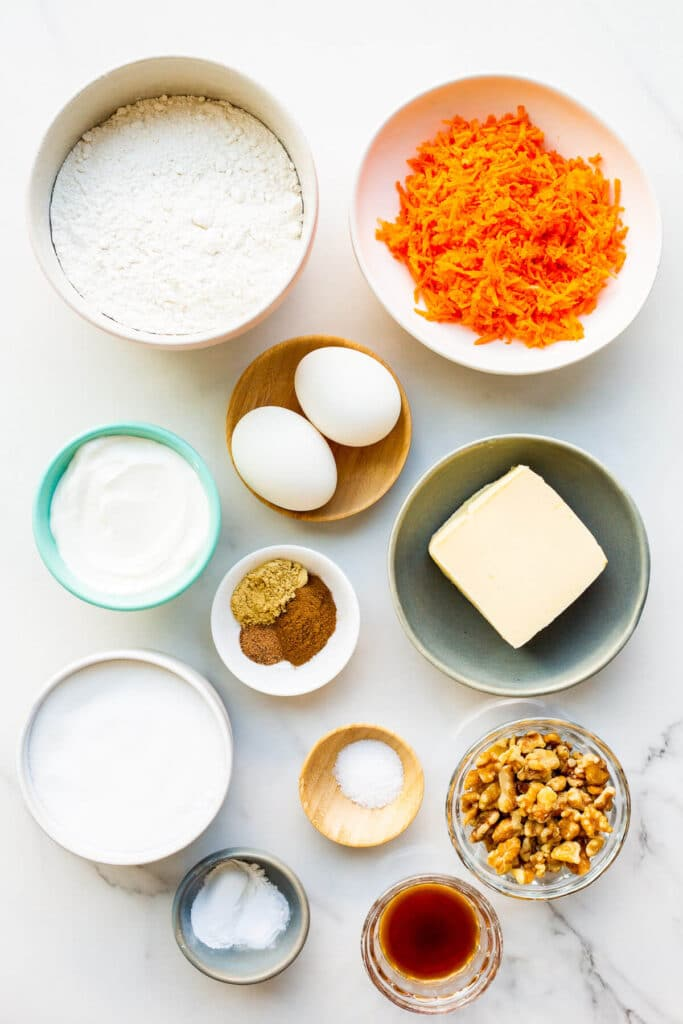 Ingredients measured out to make easy carrot muffins with walnuts and sour cream, ready to be mixed.