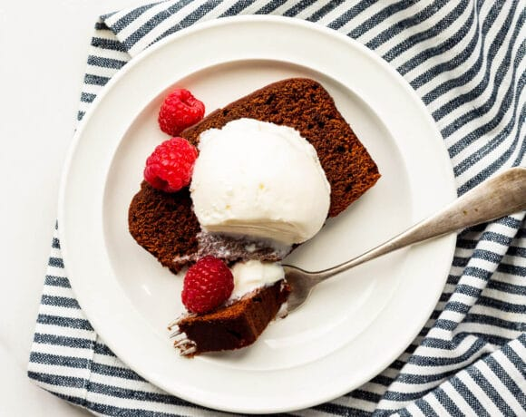 Slice of chocolate loaf cake with a scoop of ice cream and fresh raspberries on a plate with a fork, with a striped linen tucked underneath.
