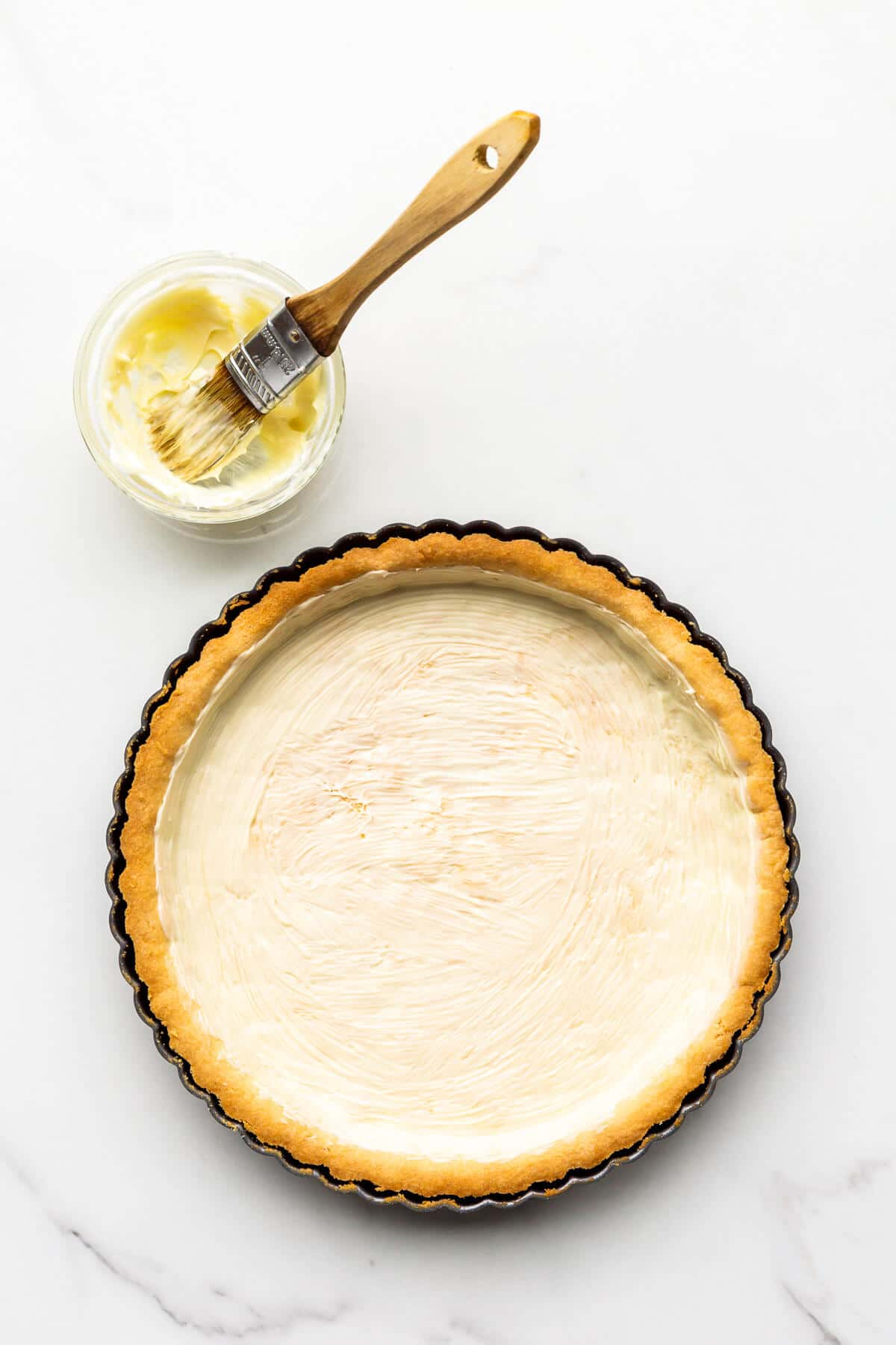 Brushing a baked tart shell with melted white chocolate to seal the pastry crust before filling.