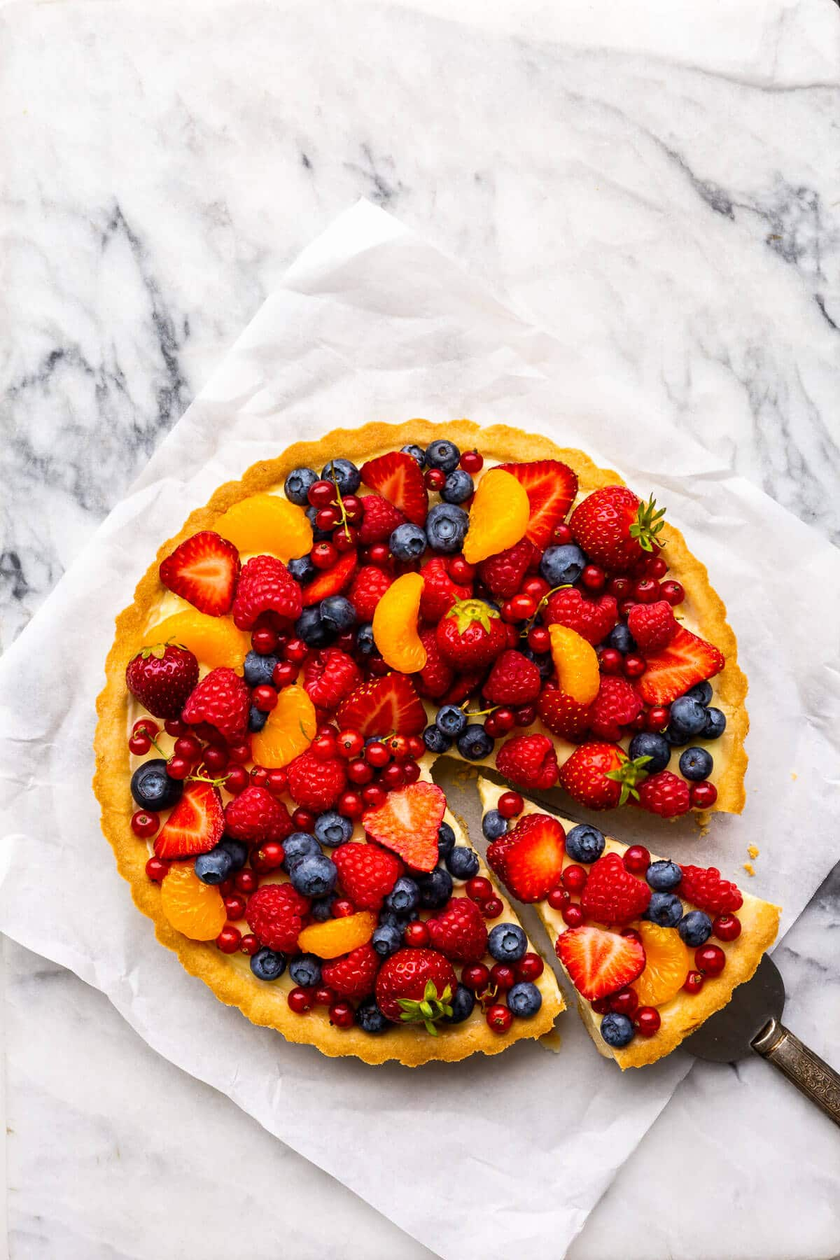Fruit tart with vanilla pastry cream and fresh berries on parchment paper on marble.