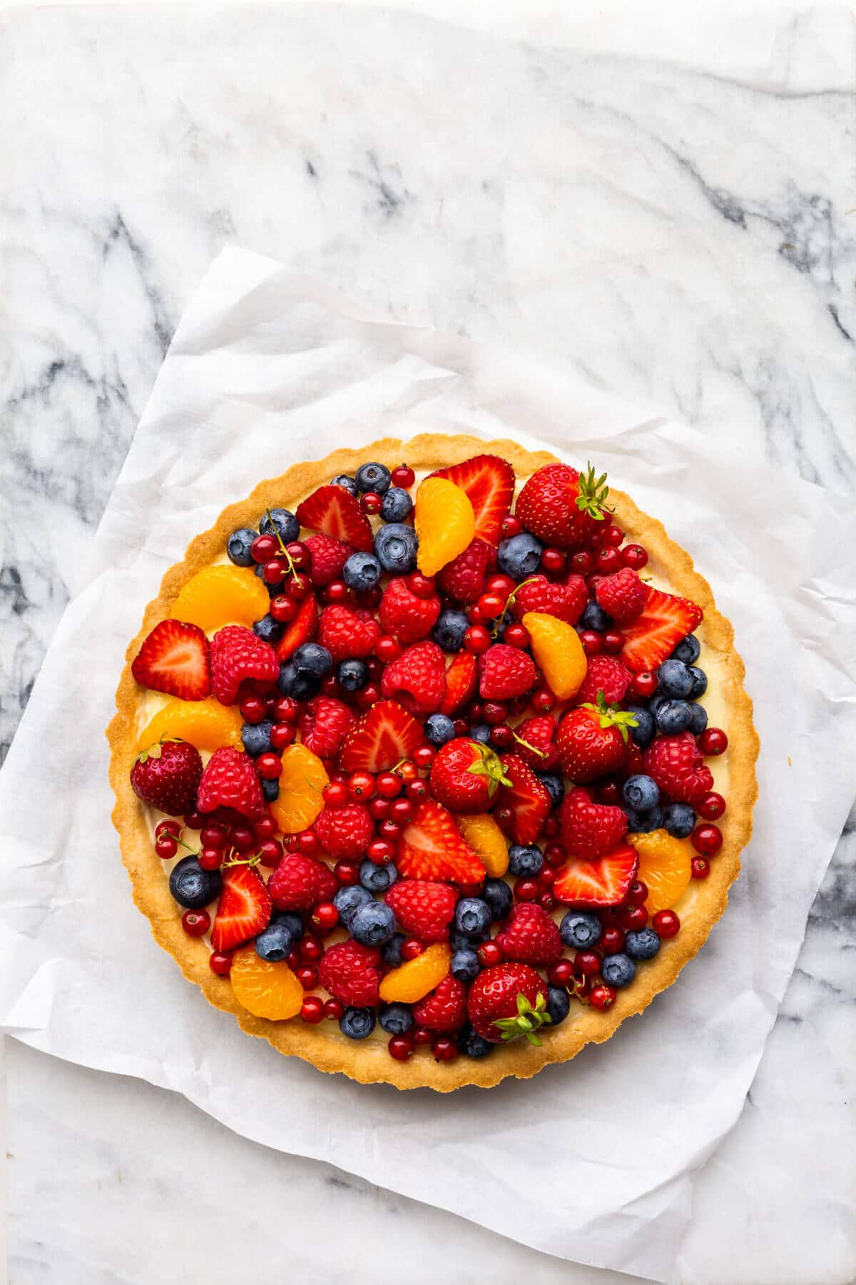 Fruit tart with vanilla pastry cream on parchment paper on marble.