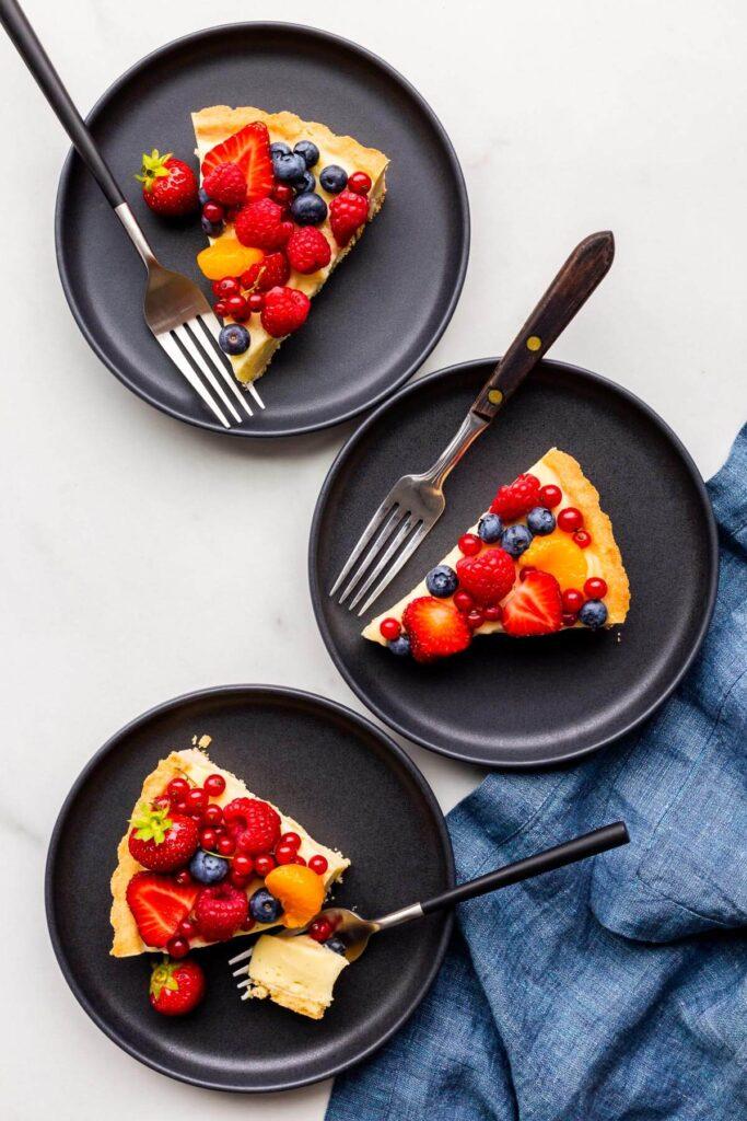 Slices of fruit tart served on black dessert plates.
