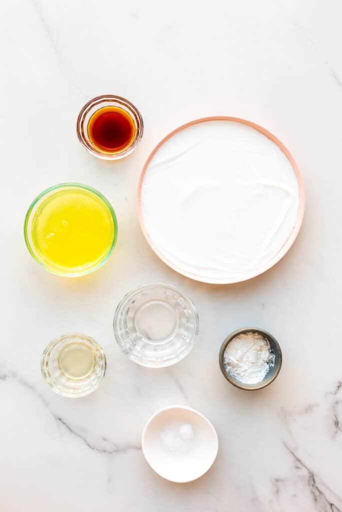 Ingredients measured out to make a pavlova from scratch from egg whites, super fine sugar, cream of tartar, cornstarch, vinegar, vanilla, and salt.