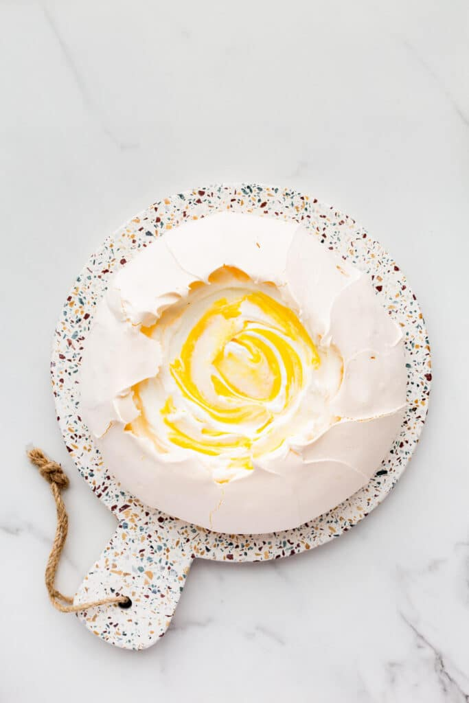Pavlova cake filled with whipped cream and lemon curd.