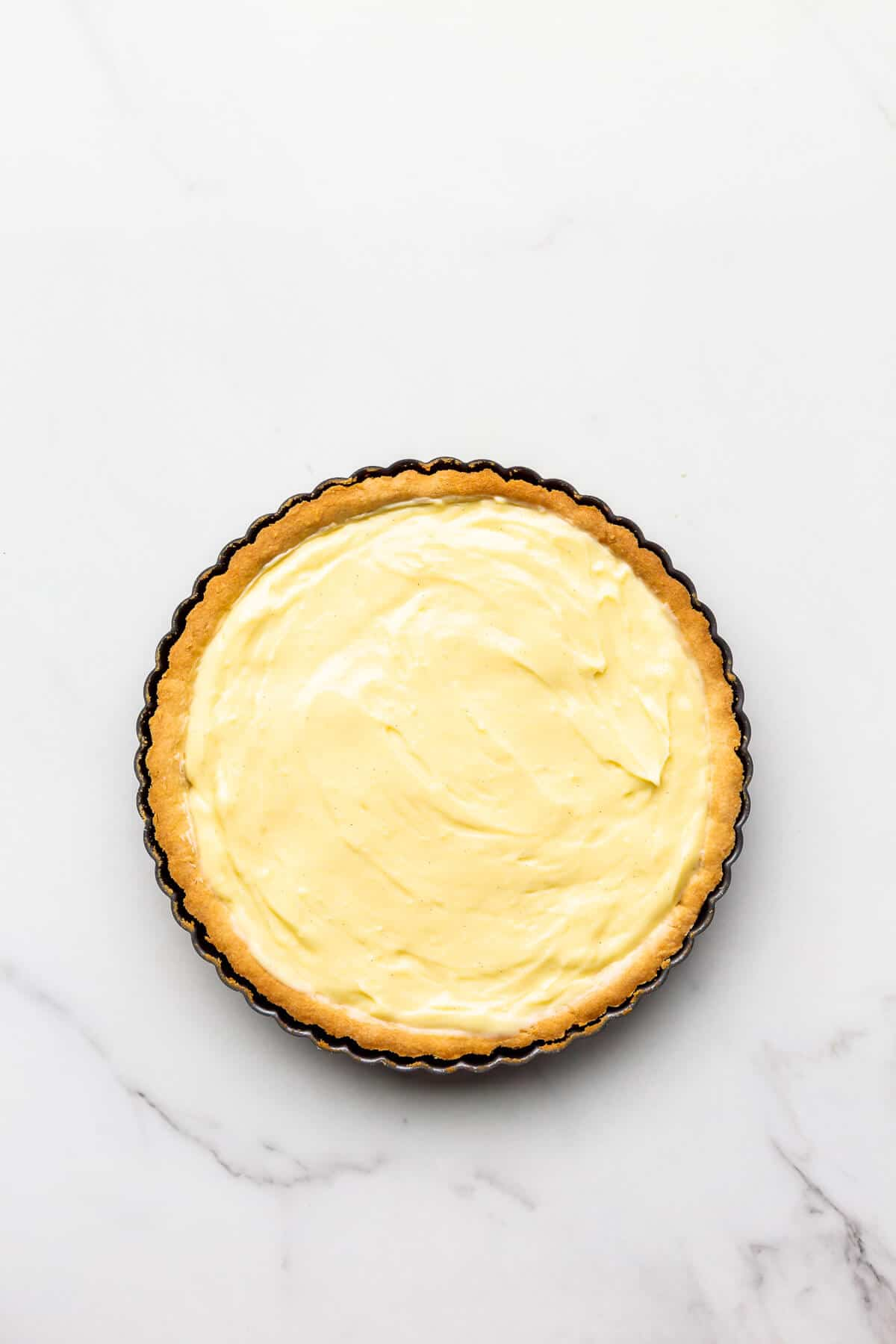 Baked tart shell filled with pastry cream.