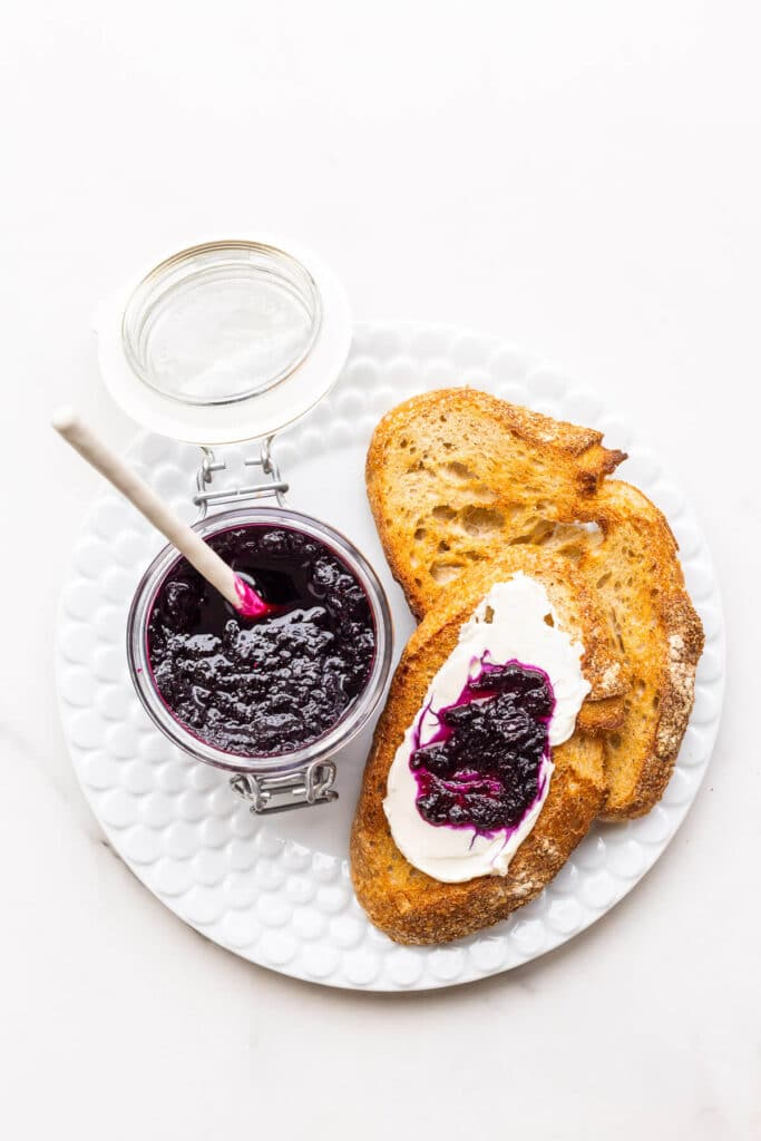A jar of homemade blueberry jam served with cream cheese and toasted sourdough on a plate.