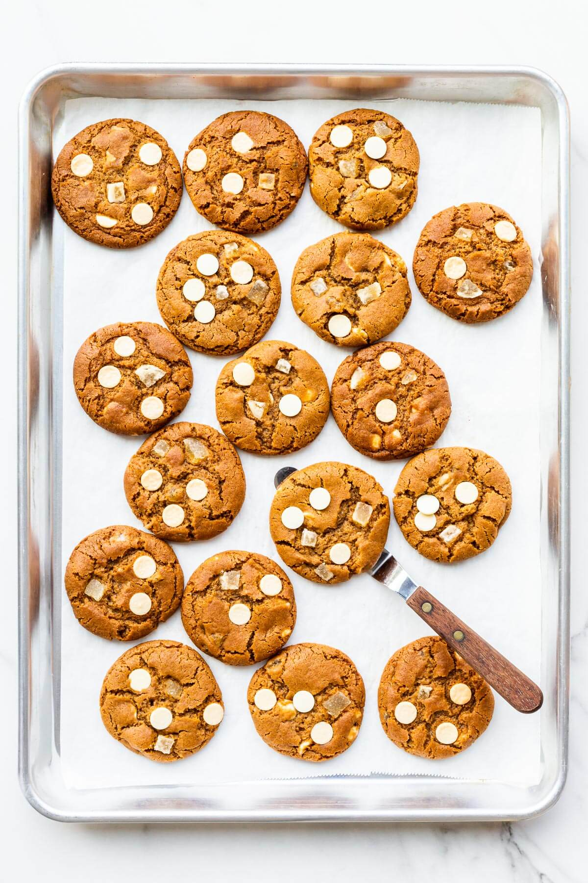 Freshly baked ginger white chocolate cookies cooling slightly on a sheet pan to firm them up before transferring to a cooling rack.