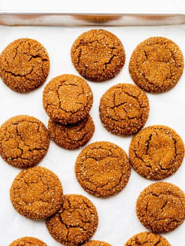 Freshly baked molasses cookies coated in turbinado sugar on a parchment-lined sheet pan.