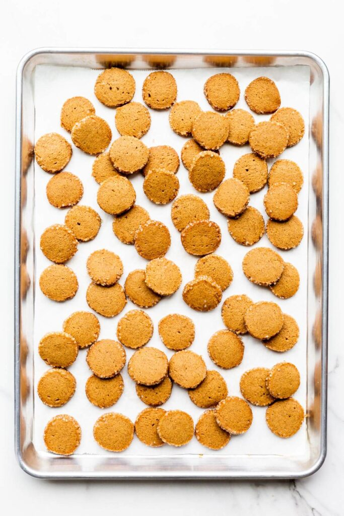A sheet pan of gingerbread cookie coins with crunchy turbinado edges.