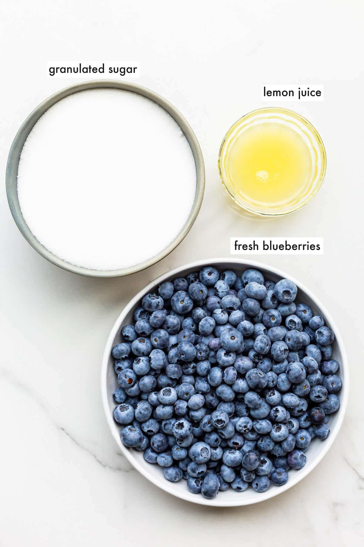 The three ingredients needed to make homemade blueberry jam, including fresh blueberries, granulated sugar, and lemon juice.
