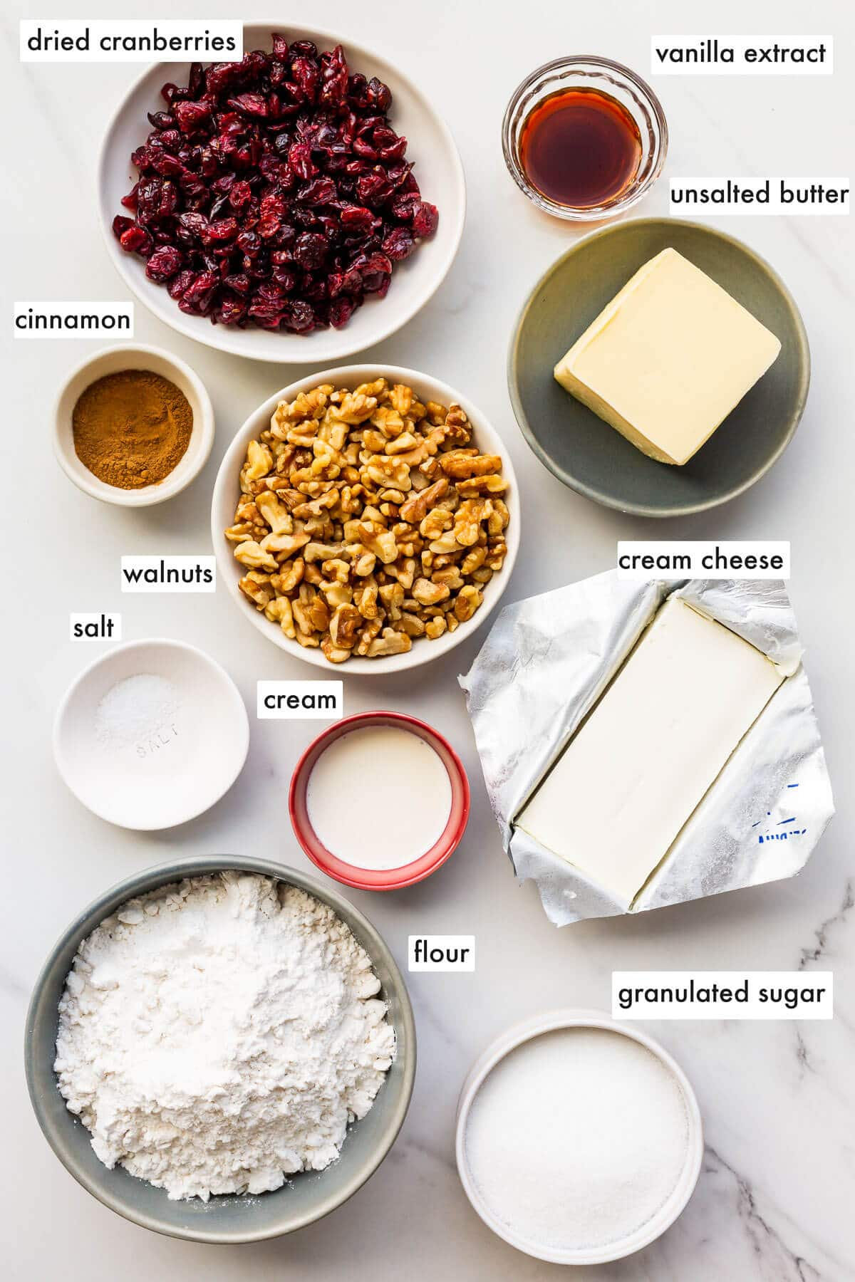 Ingredients to make rugelach with a cream cheese dough and filled with cinnamon, walnuts, and dried cranberries.