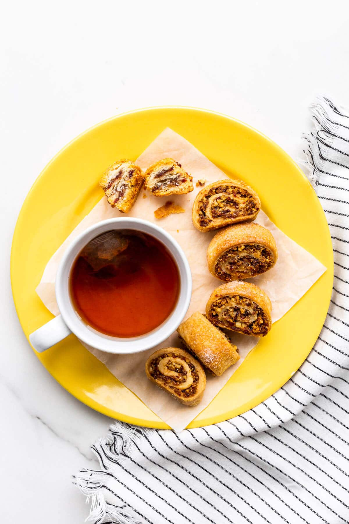 Rugelach cookies on a yellow plate with a cup of tea.
