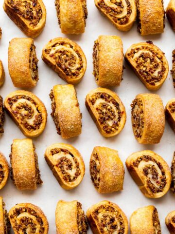 Rugelach cookies, freshly baked, lined up on parchment paper to show the beautiful swirls of cream cheese cookie dough and cinnamon walnut filling.