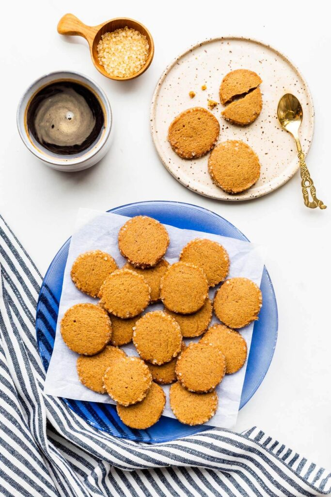 A plate of round gingerbread cookies with crunchy turbinado sugar edges served with a cup of coffee.