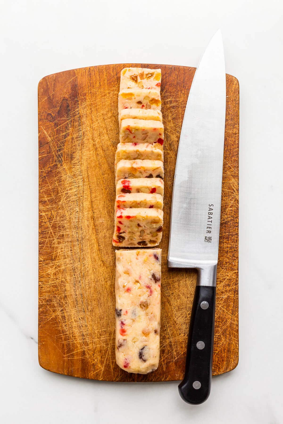 Slicing a log of fruitcake cookie dough on a wood cutting board.