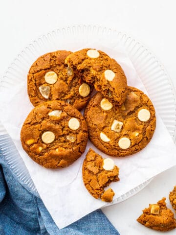A plate of ginger cookies with white chocolate chips.