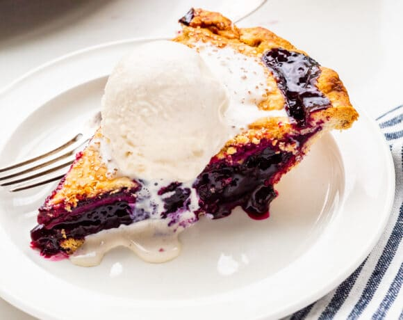A slice of blueberry pie served à la mode with a scoop of vanilla ice cream on top, melting slowly.