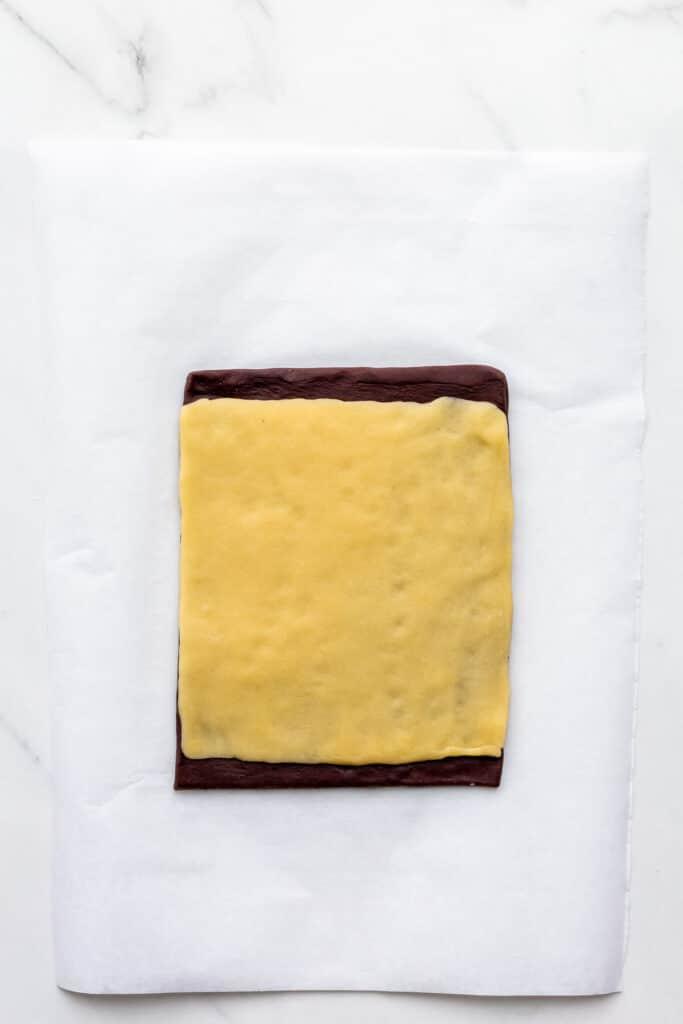 Stacking chocolate and vanilla cookie dough to make pinwheel cookies.
