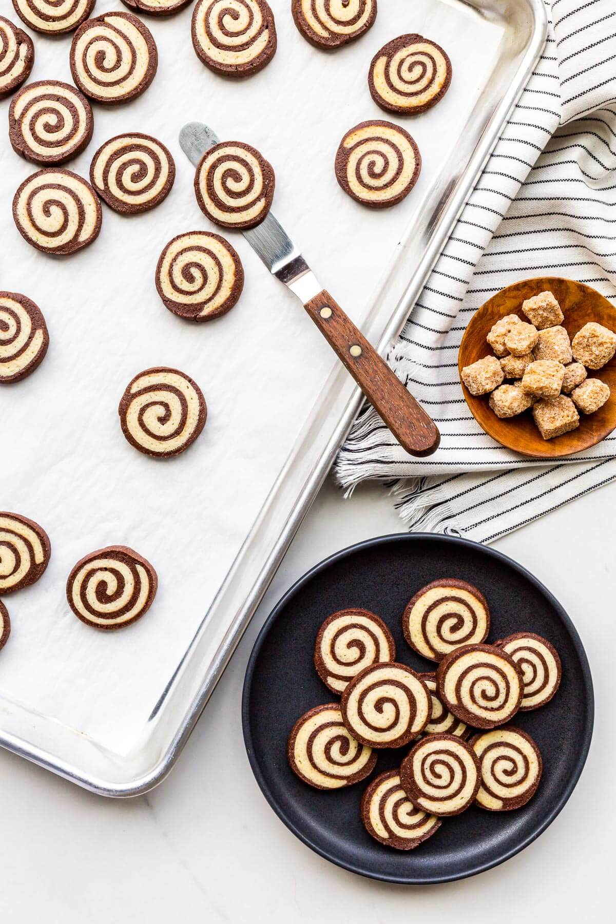 Transferring pinwheel cookies from a sheet pan to a plate to serve them.