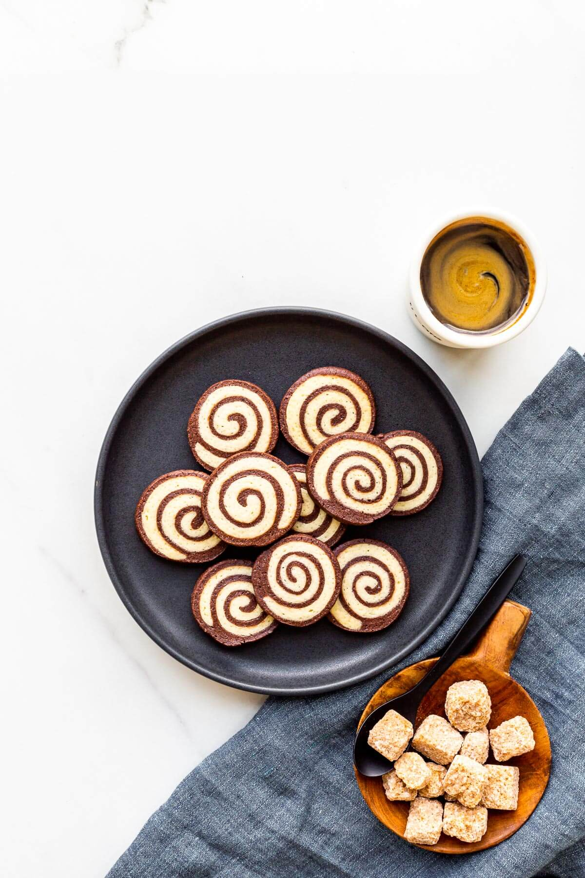 A plate of pinwheel cookies served with a cup of coffee and a bowl sugar cubes.