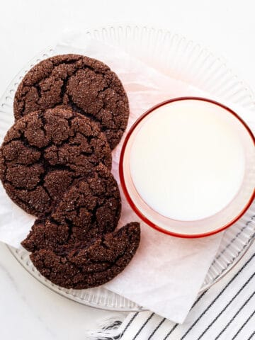A plate of chocolate sugar cookies and a glass of milk.
