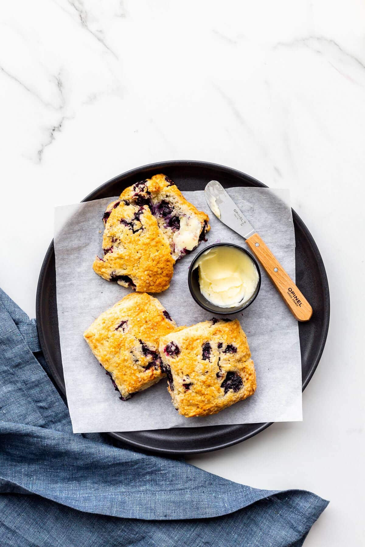 A plate of blueberry scones served with butter.