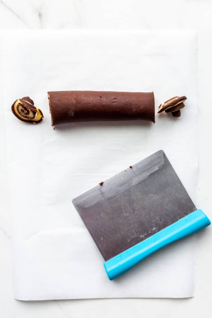 Slicing the ends of a log of pinwheel cookie dough with a pastry cutter/bench scraper.