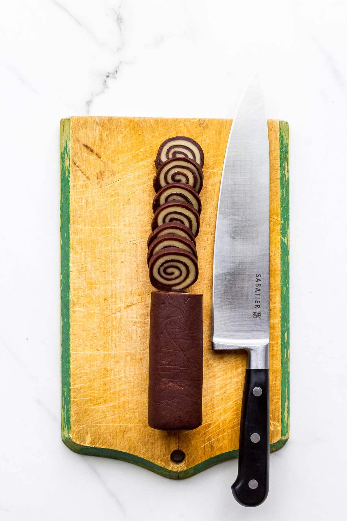 Slicing a log of cookie dough to make slice-and-bake pinwheel cookies.
