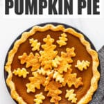 Pumpkin pie topped with leaf-shaped pie crust cookie cutouts to decorate it.