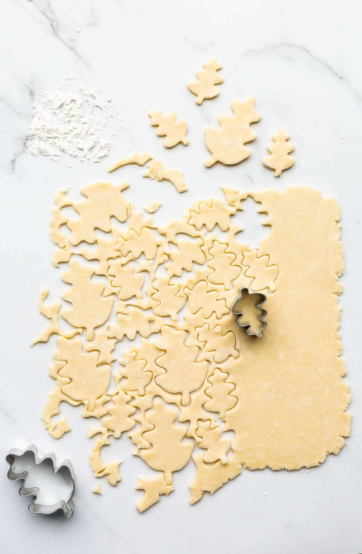 Cutting out pie crust cookies from leftover pie dough. These can be baked to eat as cookies or used to decorate a pumpkin pie.