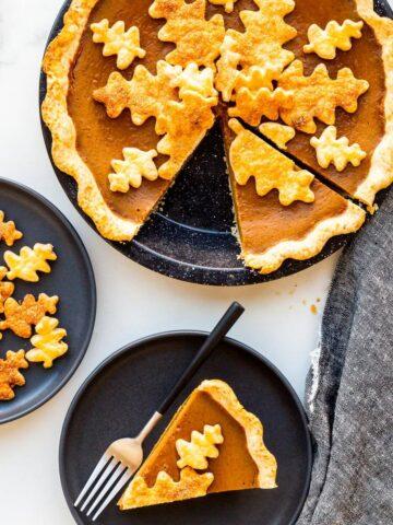 Serving pumpkin pie on black plates.