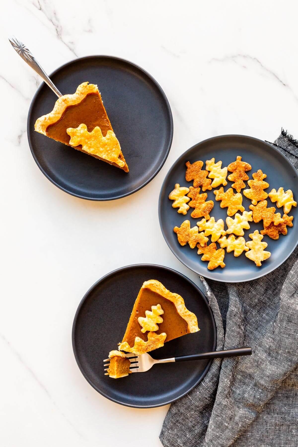 Slices of pumpkin pie served on black plates.