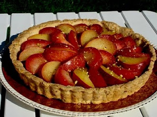 Pluot pistachio tart on a decorative plate with sliced fresh pluots on top